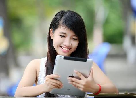 ipadを笑顔で操作する女性